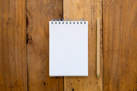Top view mockup image of notebook and pencil on vintage wooden background