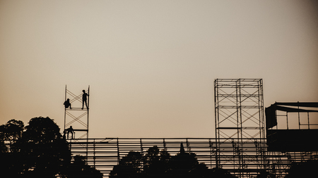 Silhouette image of a group of workers working on scaffolding for construction in the evening