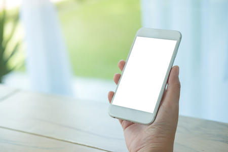 Mockup image of hand holding white mobile phone with blank screen on table in cafe 写真素材
