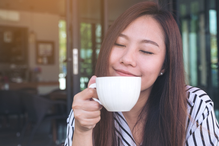 Closeup image of a beautiful Asian woman closing her eyes , smelling before drinking hot coffee with feeling good in cafe Imagens
