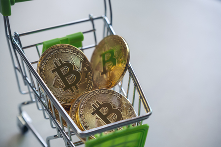 A golden bitcoins in a cart with white background
