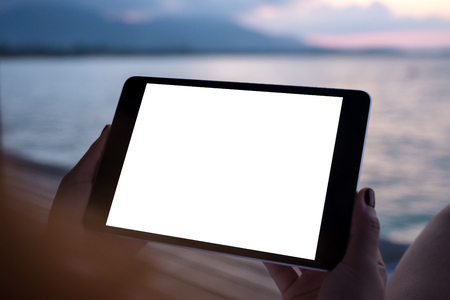Mockup image of a woman's hands holding a black tablet with blank white desktop screen by the sea with sunset background