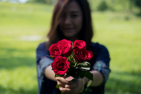 Blur Asian women giving red roses flower to her boyfriend on Valentines day with green grass background