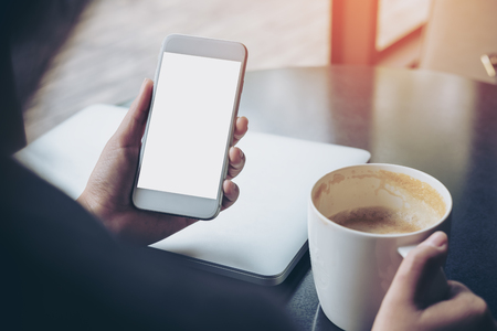 Mockup image of business woman holding mobile phone with blank white screen with latop and coffee cup on wooden table in cafe