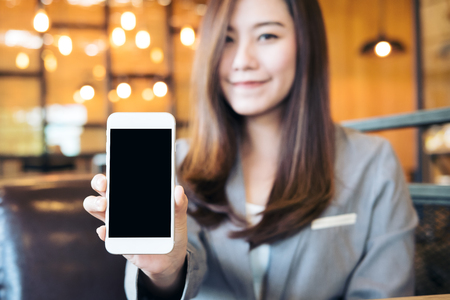 Mockup image of an Asian beautiful business woman holding and showing white mobile phone with blank black screen and smiley face in cafe