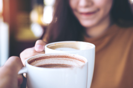 Close up image of man and woman clink coffee mugs in cafe Foto de archivo
