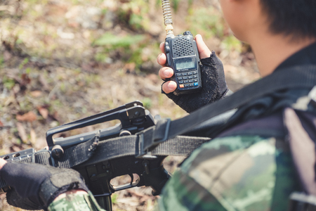 Closeup image of an armed soldier holding and using radio communication in the battle field 写真素材