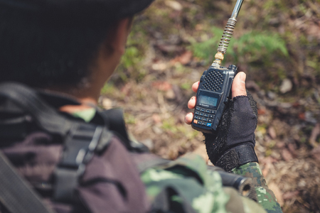 Closeup image of an armed soldier holding and using radio communication in the battle field Imagens