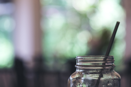 Closeup image of a glass bottle and straw with blur green nature background Archivio Fotografico