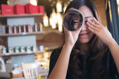 A beautiful Asian woman roll a book and looking through it with one eye while closing another eye with feeling happy , sitting in cafe Stock Photo