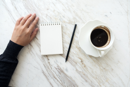 Top view image of a hand going to write down on a blank white notebook with coffee cup on table