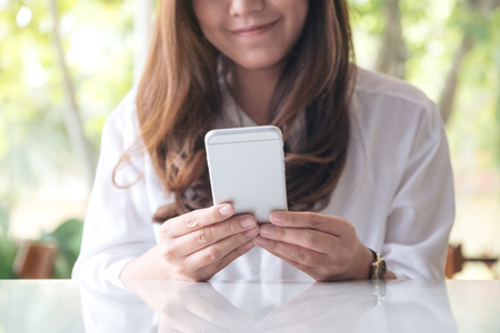 Closeup image of a beautiful Asian woman holding , using and looking at smart phone with feeling happy