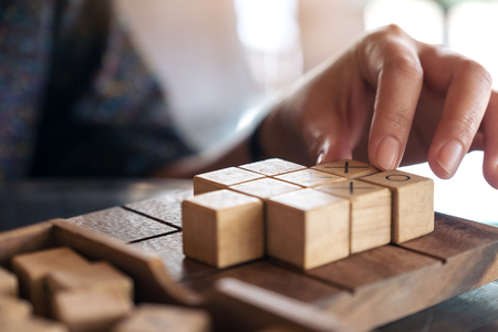 Closeup image of people playing wooden Tic Tac Toe game or OX game