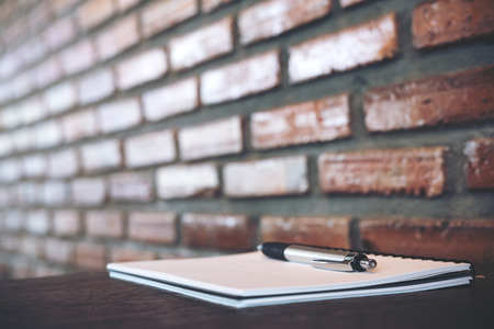 A blank white notebook and silver color pen on wooden table with brick wall background Фото со стока