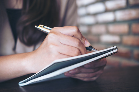 Closeup image of a business woman writing and taking note on notebook in office