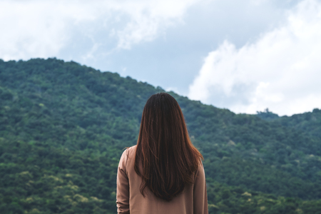 A woman turn back and standing with blue sky , green nature and mountain background