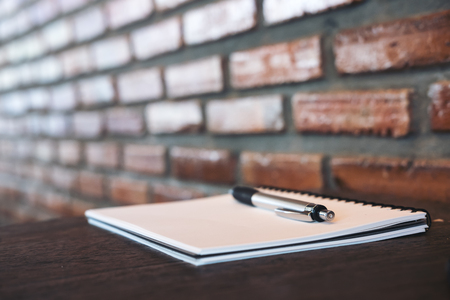 A blank white notebook and silver color pen on wooden table with brick wall background Stock Photo