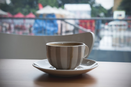 Closeup image of hot coffee cup on wooden table in cafe with outdoor background