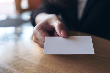 Businesswoman holding and giving  an empty business card to someone on table in office
