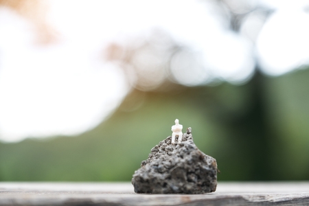 Closeup image of miniature figure model of a lonely man sitting on the rock with blur background