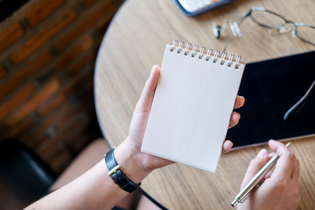 Top view image of a woman holding blank notebook with tablet on wooden table in office Stock Photo
