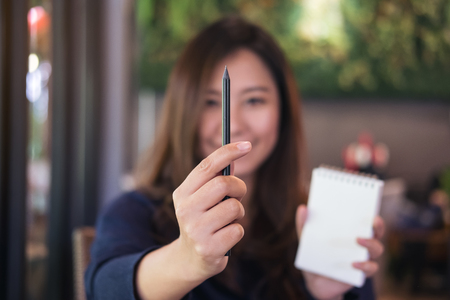 A beautiful Asian woman holding notebook and black pencil to measurement in drawing process in cafe with green vertical garden background