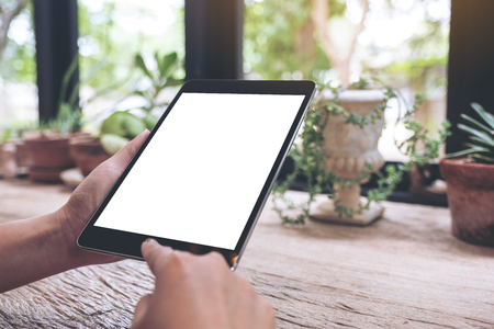 Mockup image of hands holding black tablet pc with blank white desktop screen on wooden table
