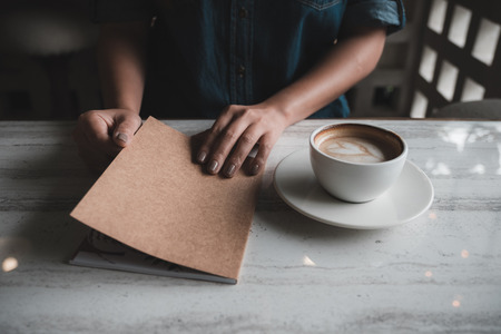 Closeup image of a woman opening a book with coffee cup in modern cafe