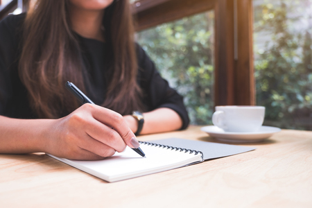Closeup image of a woman's hand writing down on a white blank notebook with coffee cup on wooden table