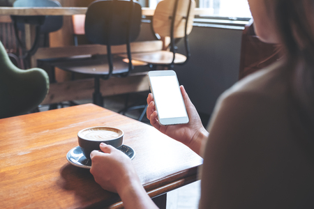 Mockup image of a woman holding white mobile phone with blank screen while drinking coffee in modern cafe