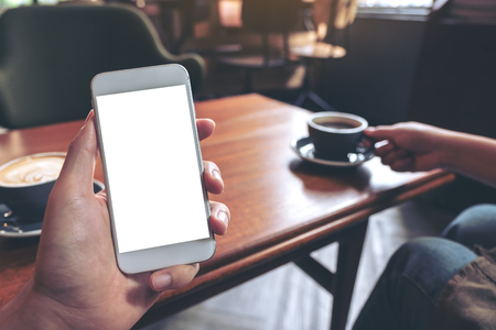 Mockup image of hand holding white mobile phone with blank screen with woman drinking coffee in modern cafe