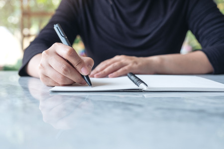 Closeup image of business woman writing on blank notebook on table with green nature background