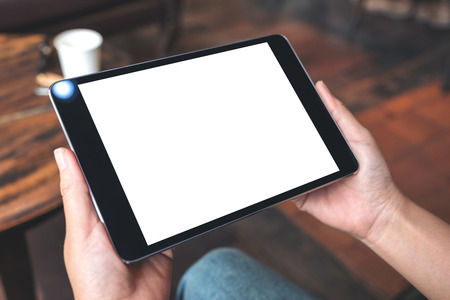 Mockup image of hands holding black tablet pc with blank white desktop screen