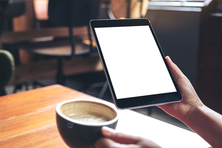 Mockup image of woman's hands holding black tablet pc with blank white screen while drinking coffee on wooden table in cafe Banco de Imagens - 109459764
