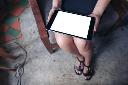 Top view mockup image of woman holding black tablet pc with blank white desktop screen while sitting in cafe