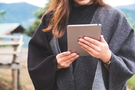Closeup image of a woman holding and using tablet pc with green nature and mountains background