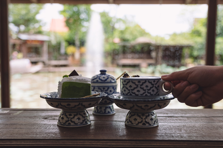 A hand holding a cup of hot milk with a piece of cake in an antique Thai traditional benjarong style containers
