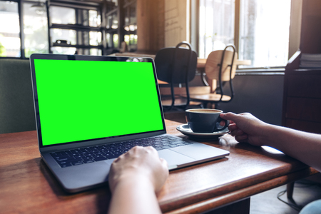 Mockup image of a woman's hands using laptop with blank desktop screen while drinking hot coffee on wooden table in cafe