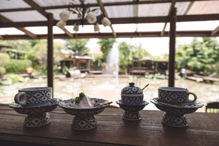 A cup of hot milk with a piece of cake in an antique Thai traditional benjarong style containers with nature background