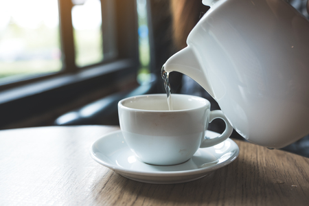 A hand holding teapot and pouring tea into a white cup on wooden table
