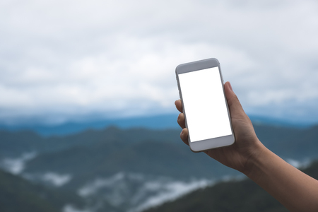 Mockup image of a hand holding and showing white smart phone with blank desktop screen in outdoor with blur green mountains background Banco de Imagens