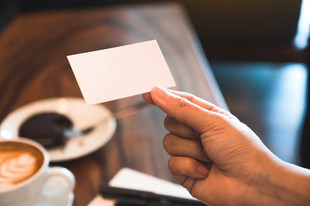 A hand holding white empty business card with notebook and coffee cup on wooden table Banco de Imagens - 109459766