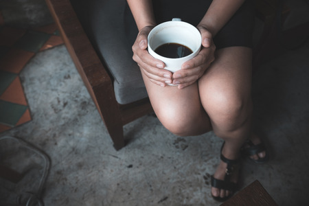 Closeup image of a woman holding a white cup of hot coffee while sitting in cafe