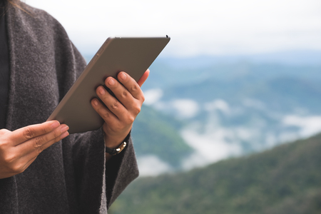Closeup image of a woman holding and using tablet pc with green mountains on foggy day with blue sky background Banco de Imagens