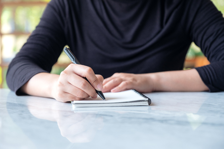 Closeup image of a woman writing on blank notebook on table with green nature background