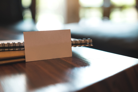 Closeup image of a white blank business card with notebooks on vintage wooden table Banco de Imagens