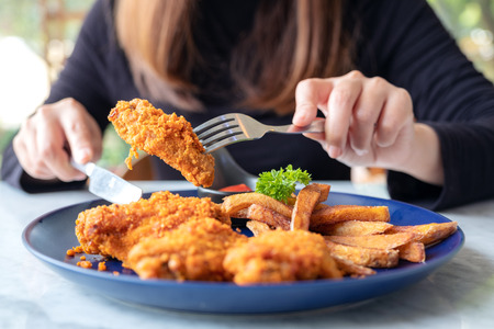 Closeup image of a woman using knife and fork to eat fried chicken and french fries in restaurant Banco de Imagens - 109459469