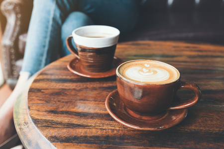 Closeup image of two cups of hot latte coffee and black coffee on vintage wooden table in cafe Banco de Imagens