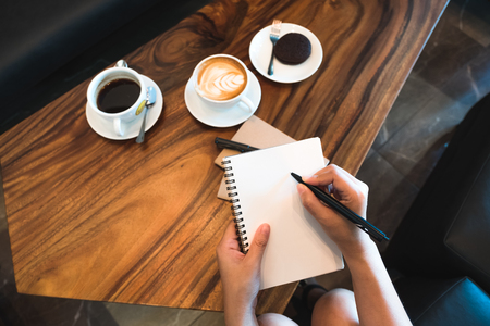 Top view image of a woman's hands holding and writing down on a white blank notebook with coffee cups on wooden table in cafe Banco de Imagens - 109459480
