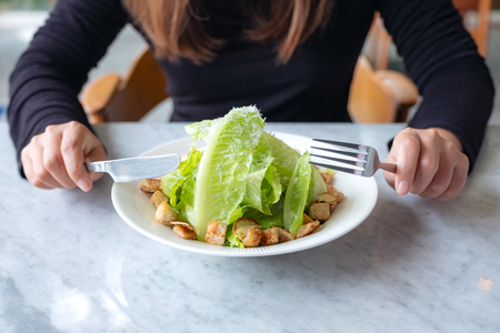 Closeup image of a woman eating caesar salad by knife and fork on table in the restaurant Banco de Imagens - 109459493